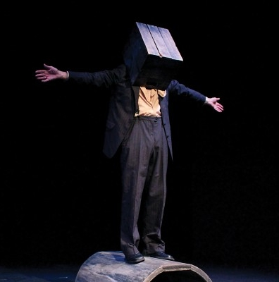 Picutre from the show: Man standing with wide arms and box on head